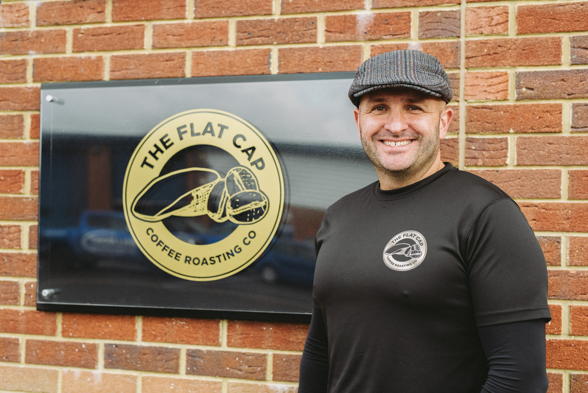 Mark, founder of Flat Cap Coffee Roasting Co. stood next to a Flat Cap Coffee sign on a wall