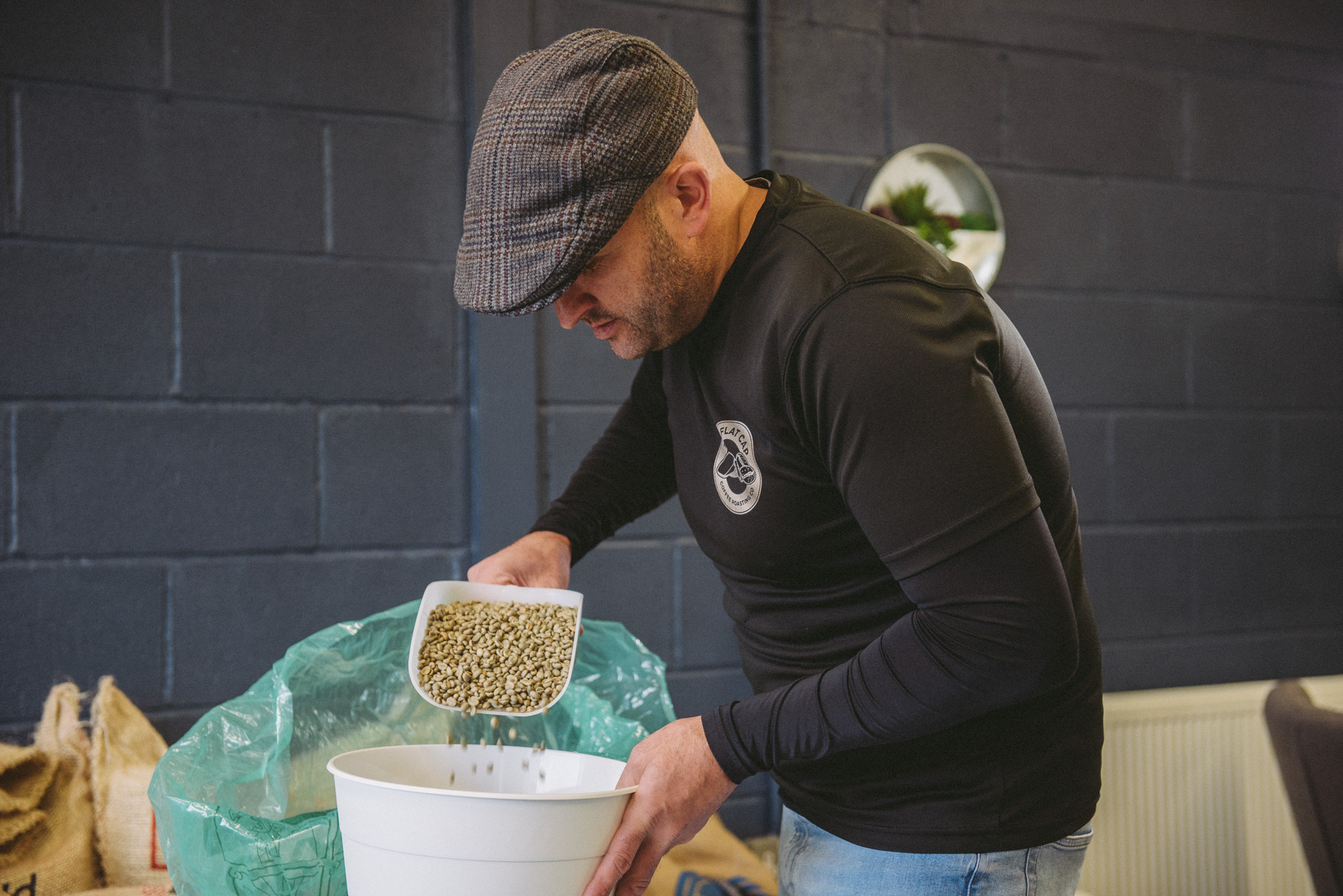 Mark of Flat Cap Coffee pouring unroasted coffee beans into a white bucket