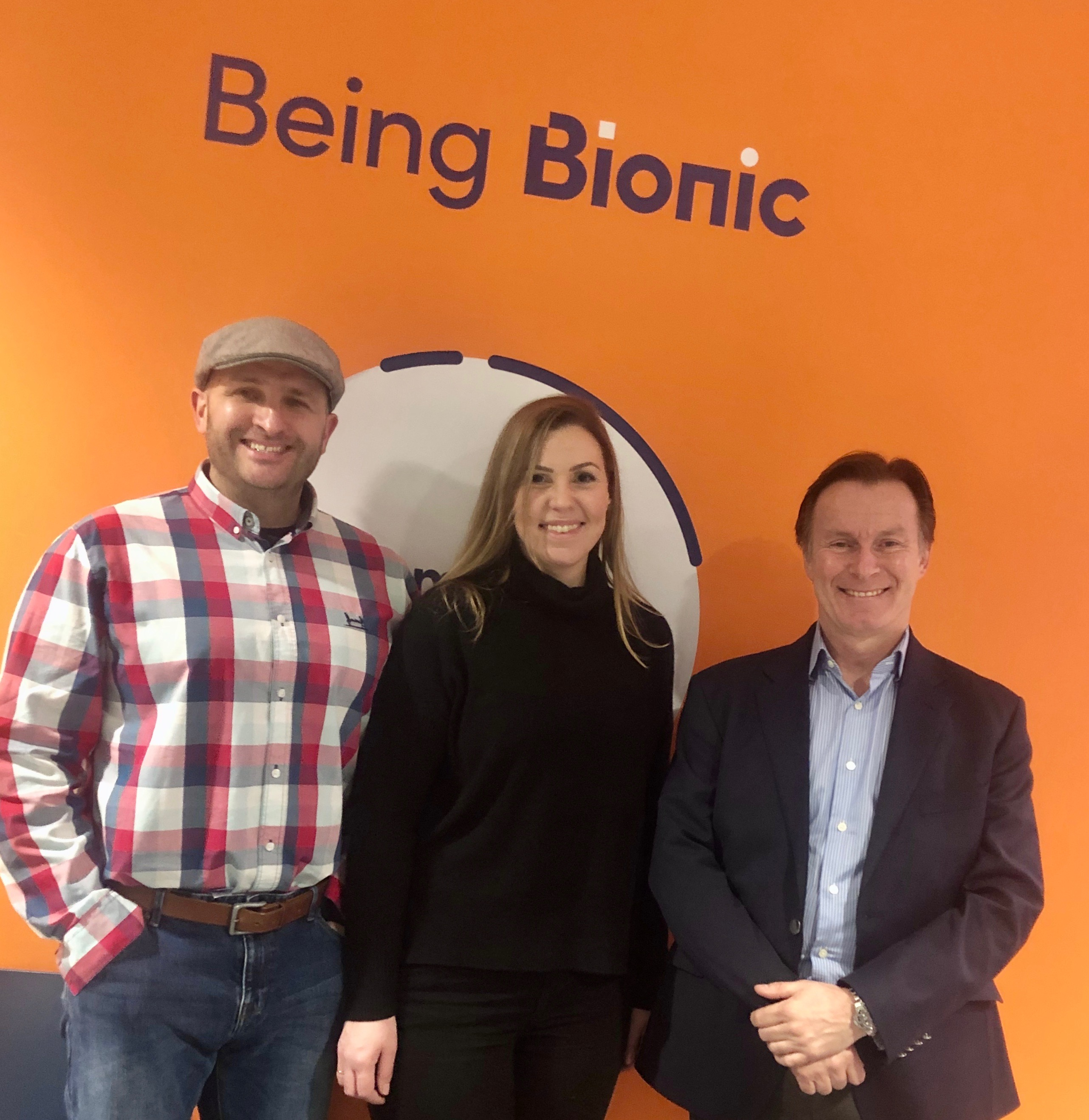 The Flat Cap team stood in front of an orange wall with Being Bionic written above them at Bionic HQ