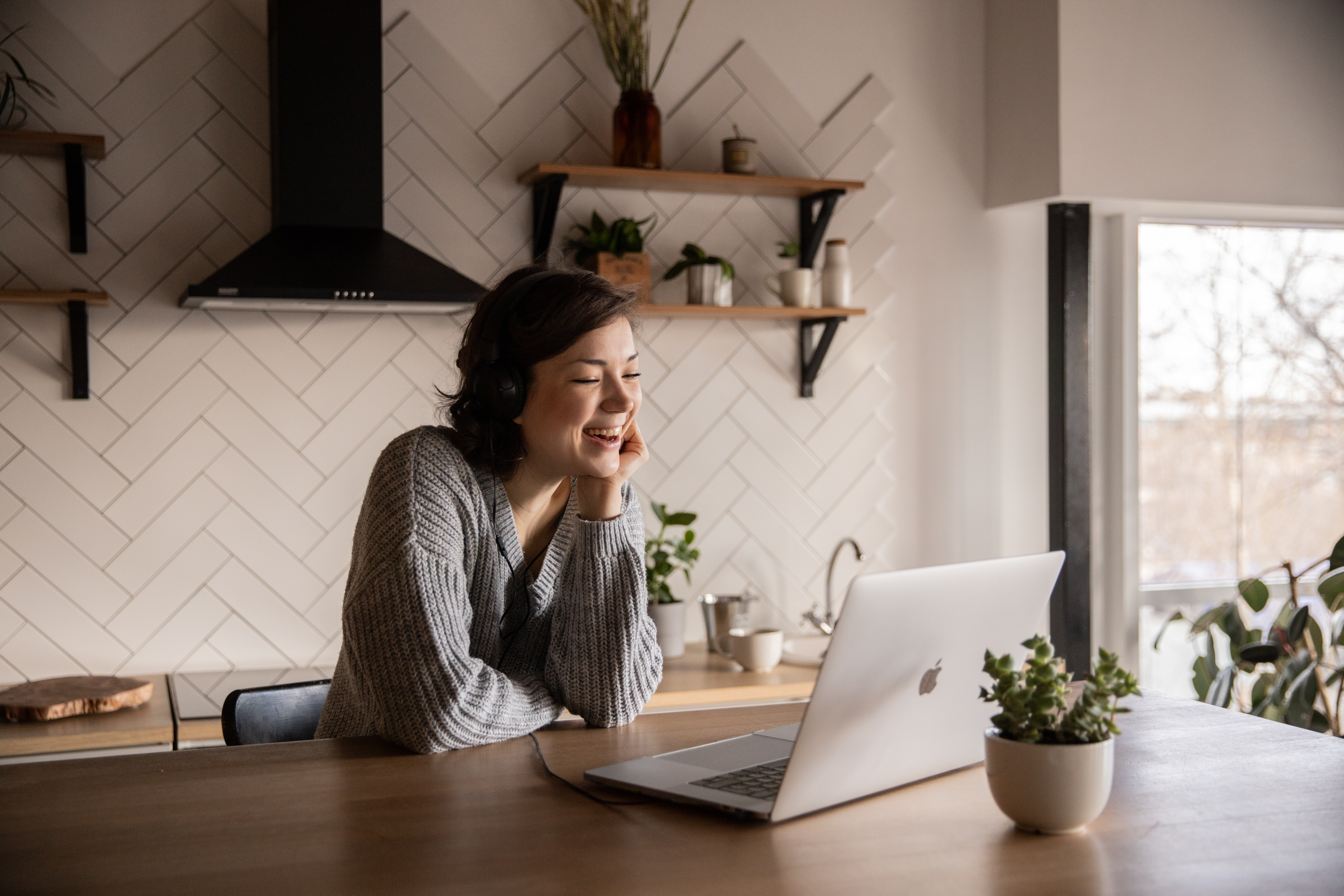 Young woman smiling at laptop in kitchen