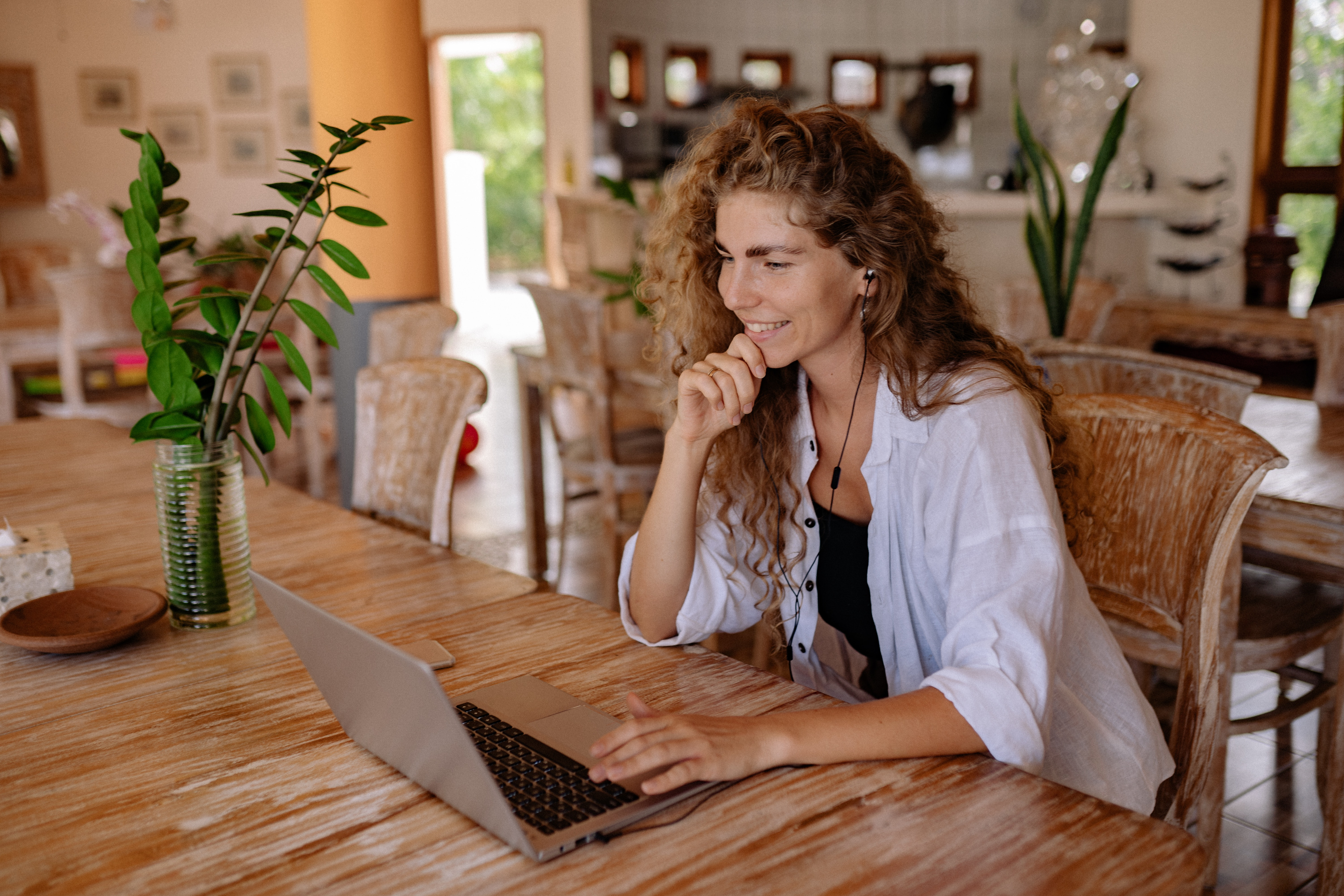 Woman smiling at laptop in an organic style home