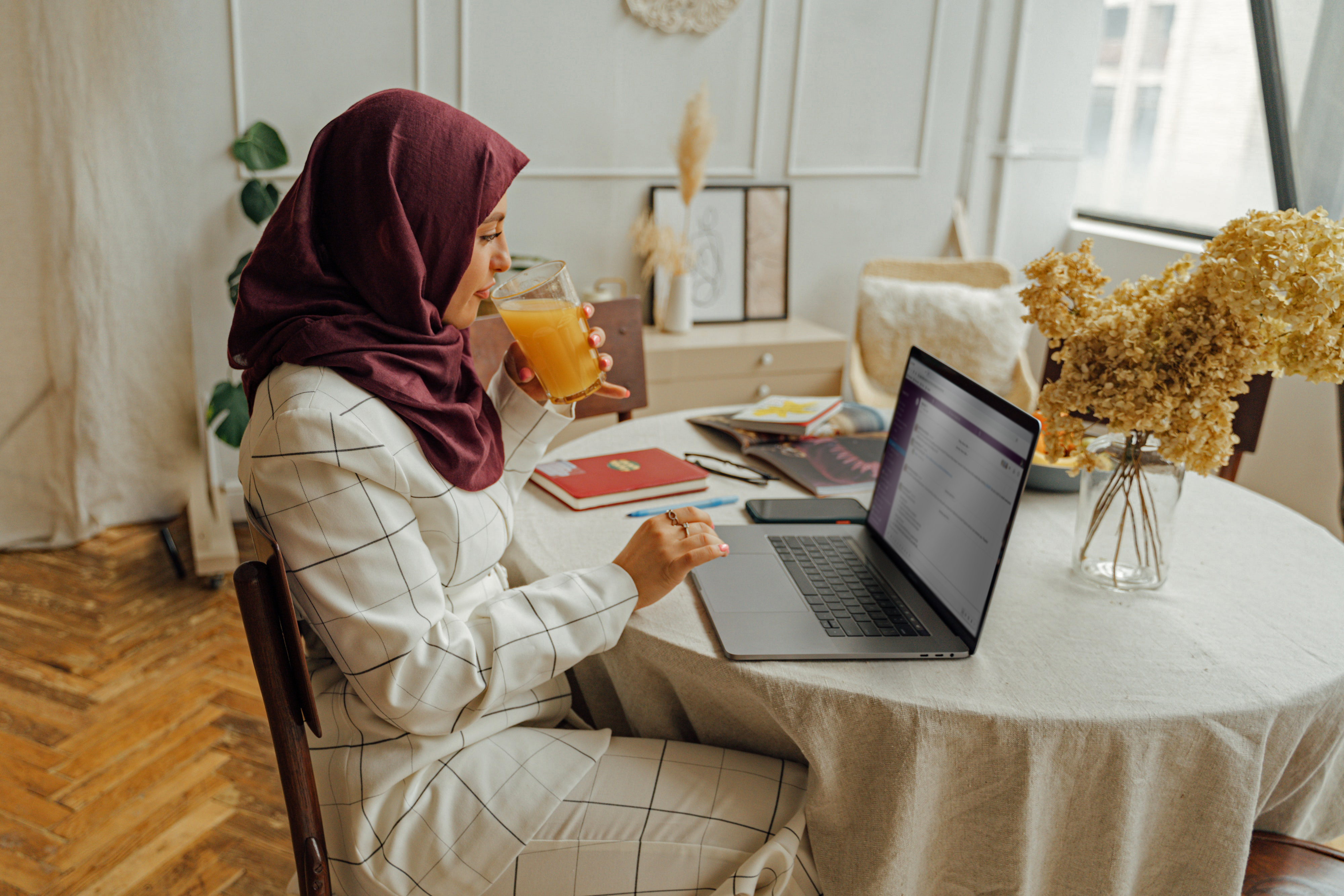 Women in home with laptop, slack on screen