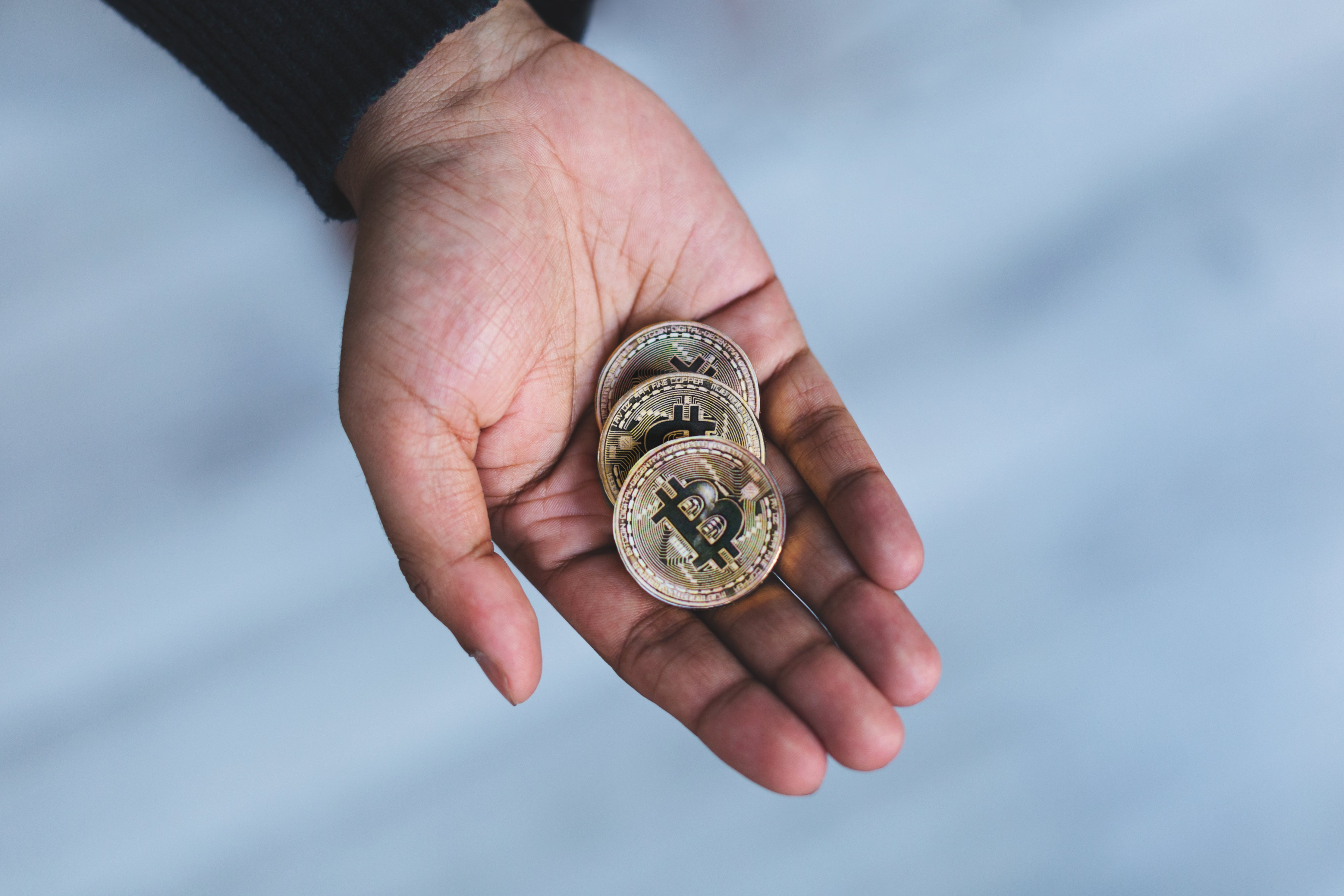 Crypto investor holding three gold btc-coins
