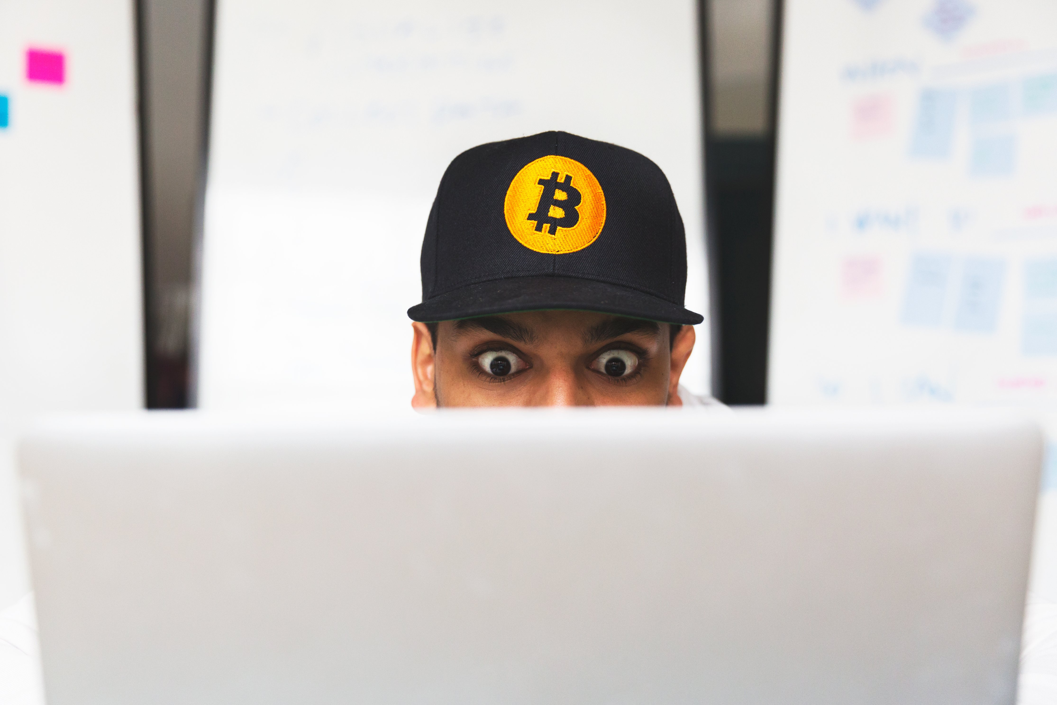 A cryptocurrency investor looking at their laptop in shock