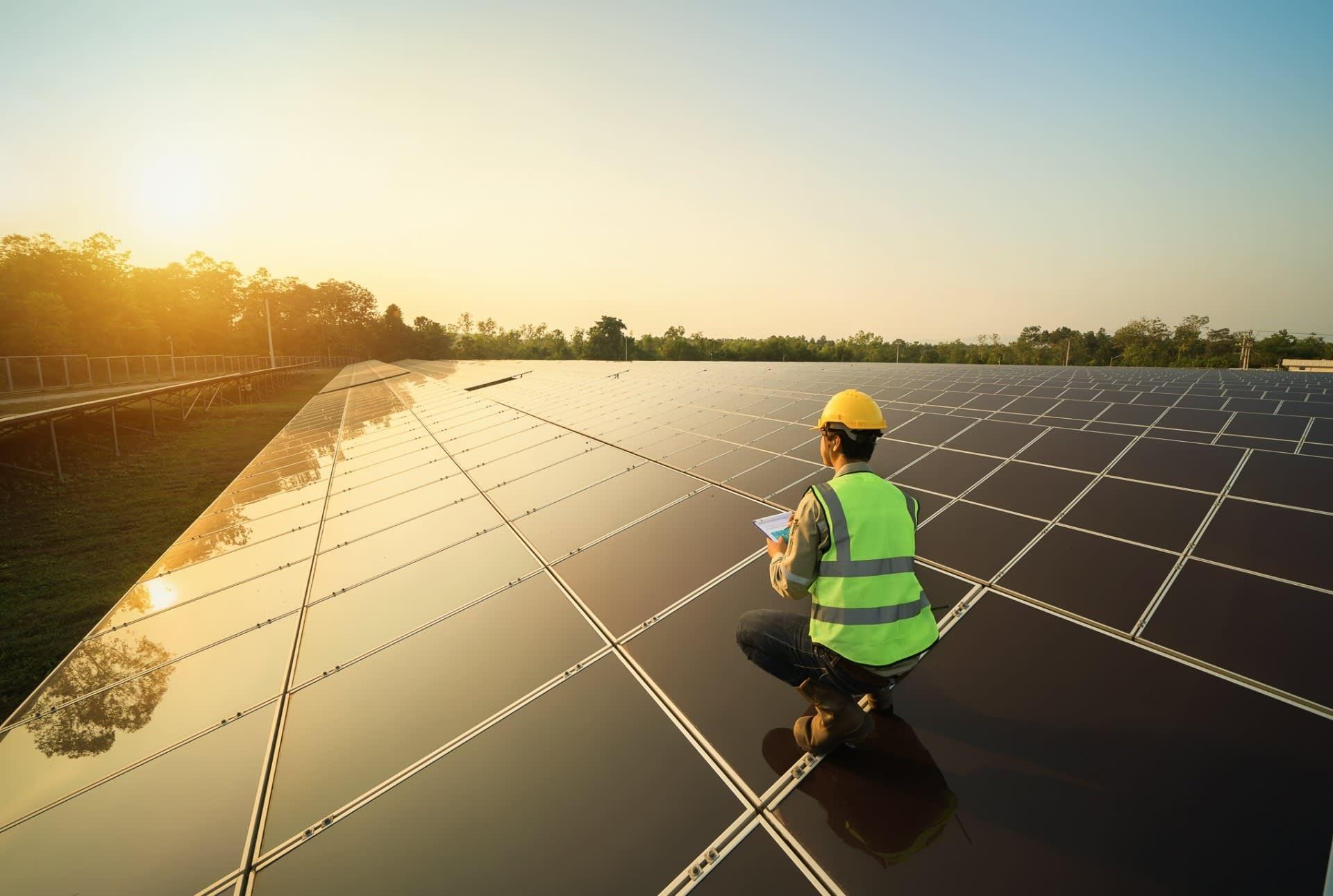 Man crouching on solar panels