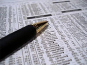 Dividend listing in newspaper with pen on top.