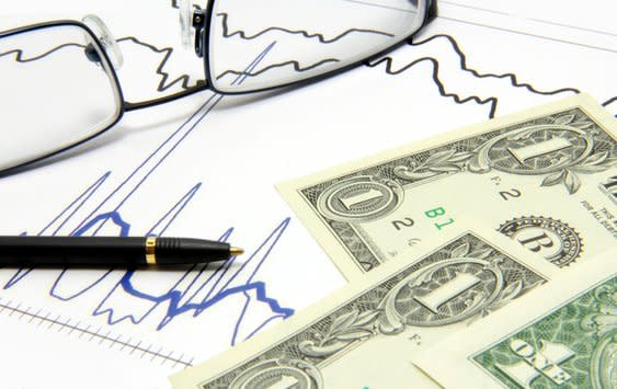 dollar bills on stock chart with pen and glasses