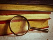 magnifying glass with stack of books