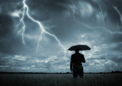 Man with umbrella looking at lightning storm.