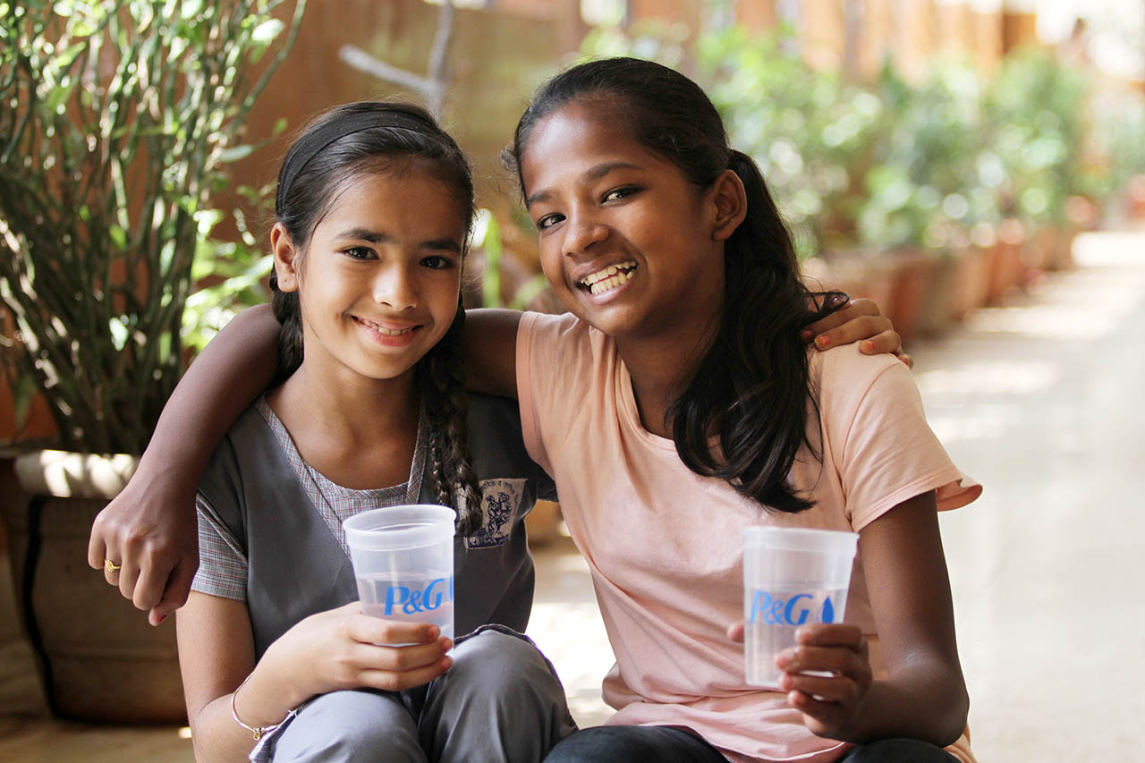 Children smiling with the glass of water