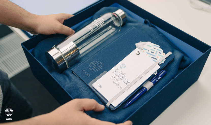 An onboarding box with a water bottle, notebook, pen, hoodie, and welcome booklet.