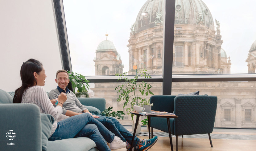 Two colleagues sitting on a couch with the Berliner Dom in the background.