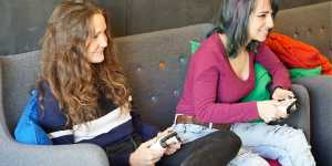 two young women sitting on a sofa playing video games and having fun while starring at a screen and holding the console controllers in their hands
