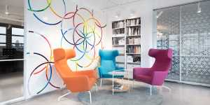 A photo of the Clue office space showing a colorful wall decorated with the Clue logo, a bookshelf, and three armchairs.