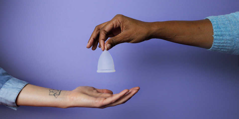 one dark-skinned hand dropping a menstrual cup into another light-skinned hand beneath it