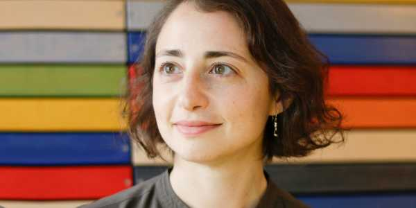 portrait of lisa kennelly in front of colorful wood panels in the clue office