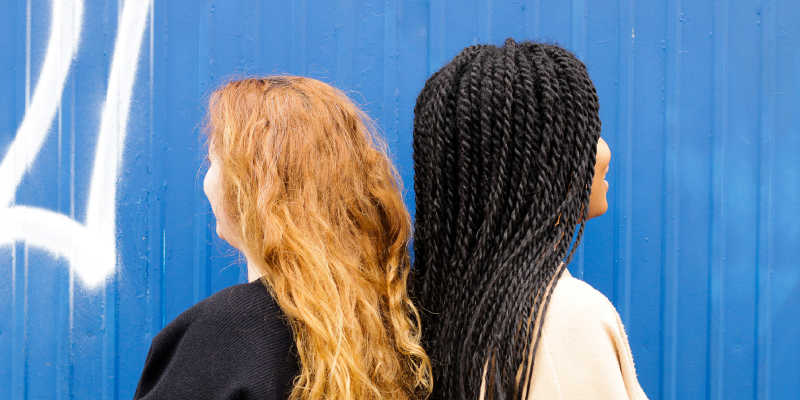 Photo of two people showing their hairstyles.