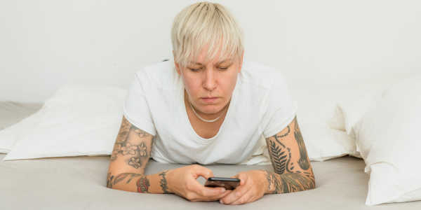 A person with short blonde hair frowns while looking at their phone.