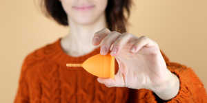 a woman holding a menstrual cup