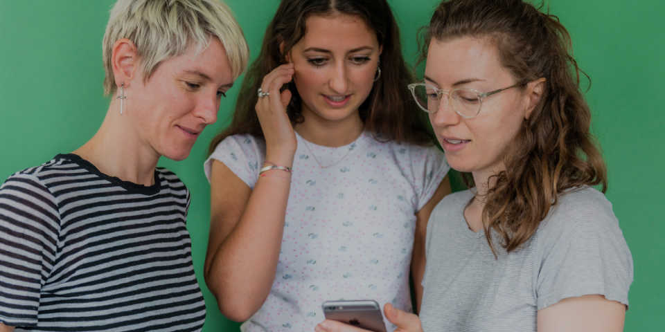 Three women looking at a phone