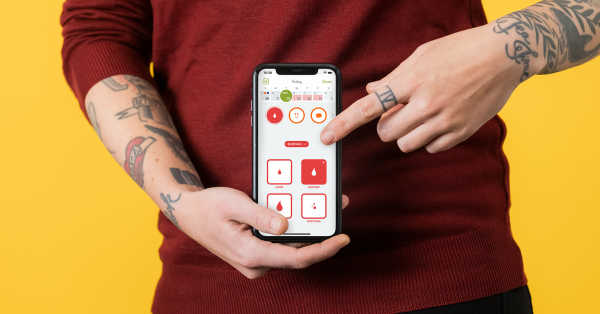 A person with tattooed arms and a red sweater holds their phone and points at the period tracking screen in the Clue app.