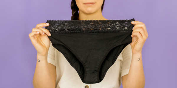 A woman holds up a pair of Flux black bikini-style period underpants, with lace trim on the waistband.