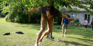 a man walking from tree to tree on a slackline in the summer