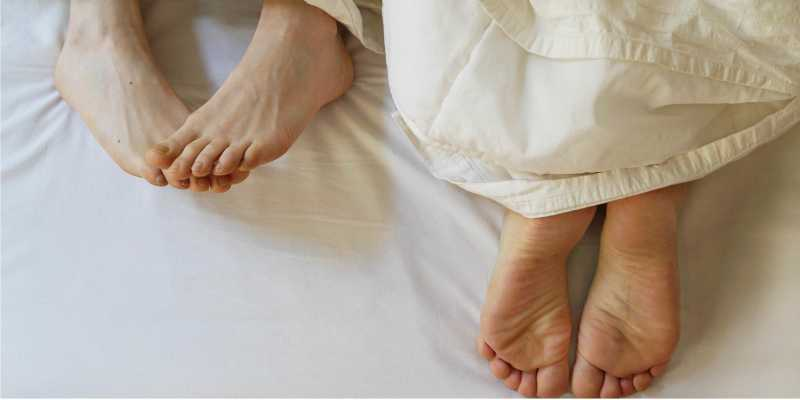 two pairs of blank feet sticking out from underneath a blanket on a matress