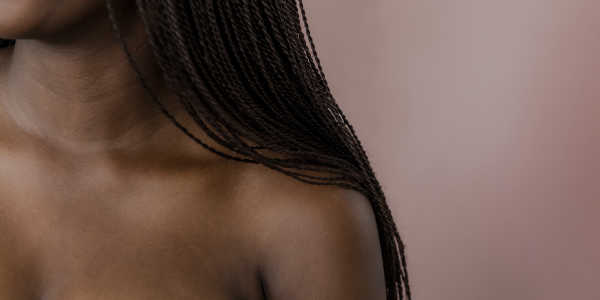 A photo of a black woman showing the shoulder, neck and hair