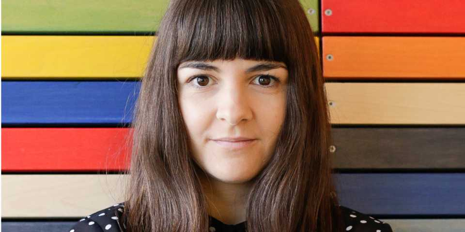 portrait of marija in front of colorful wood panels in the clue office in berlin