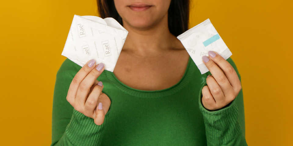 A woman holds two disposable menstrual pads in her hands.