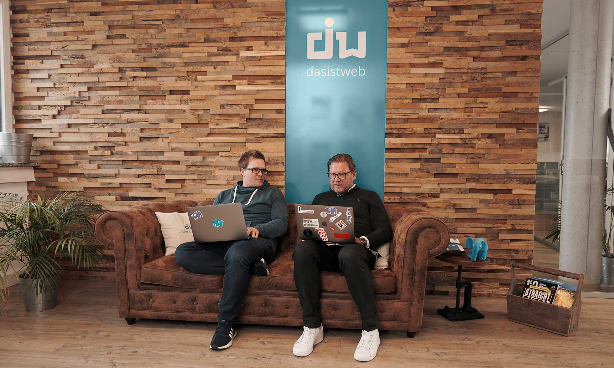 Martin Weinmayr and Andreas Rieger, CEO and Head of Sales at dasistweb sit on a sofa in their office. They are holding a laptop.