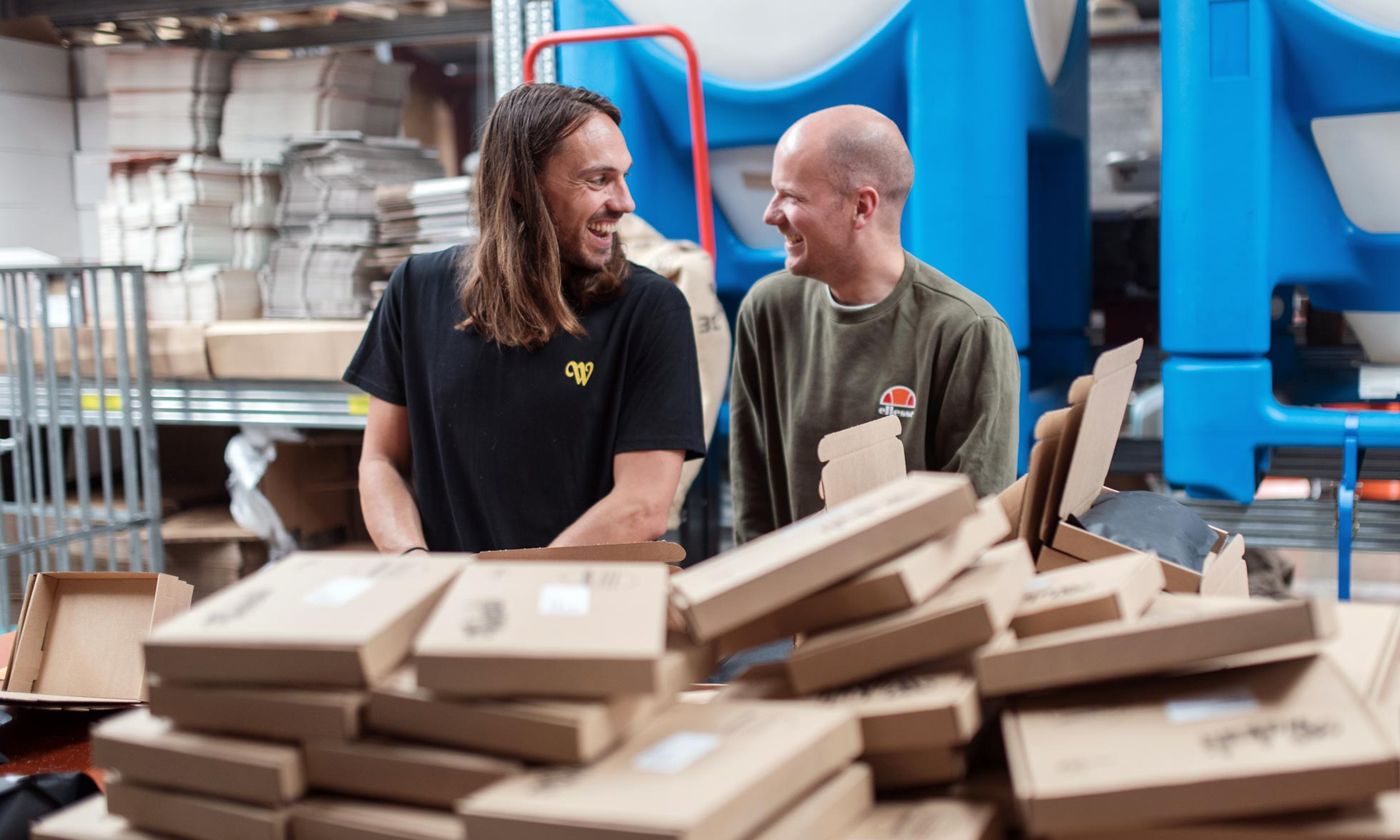 Two smiling guys behind a pile of packages