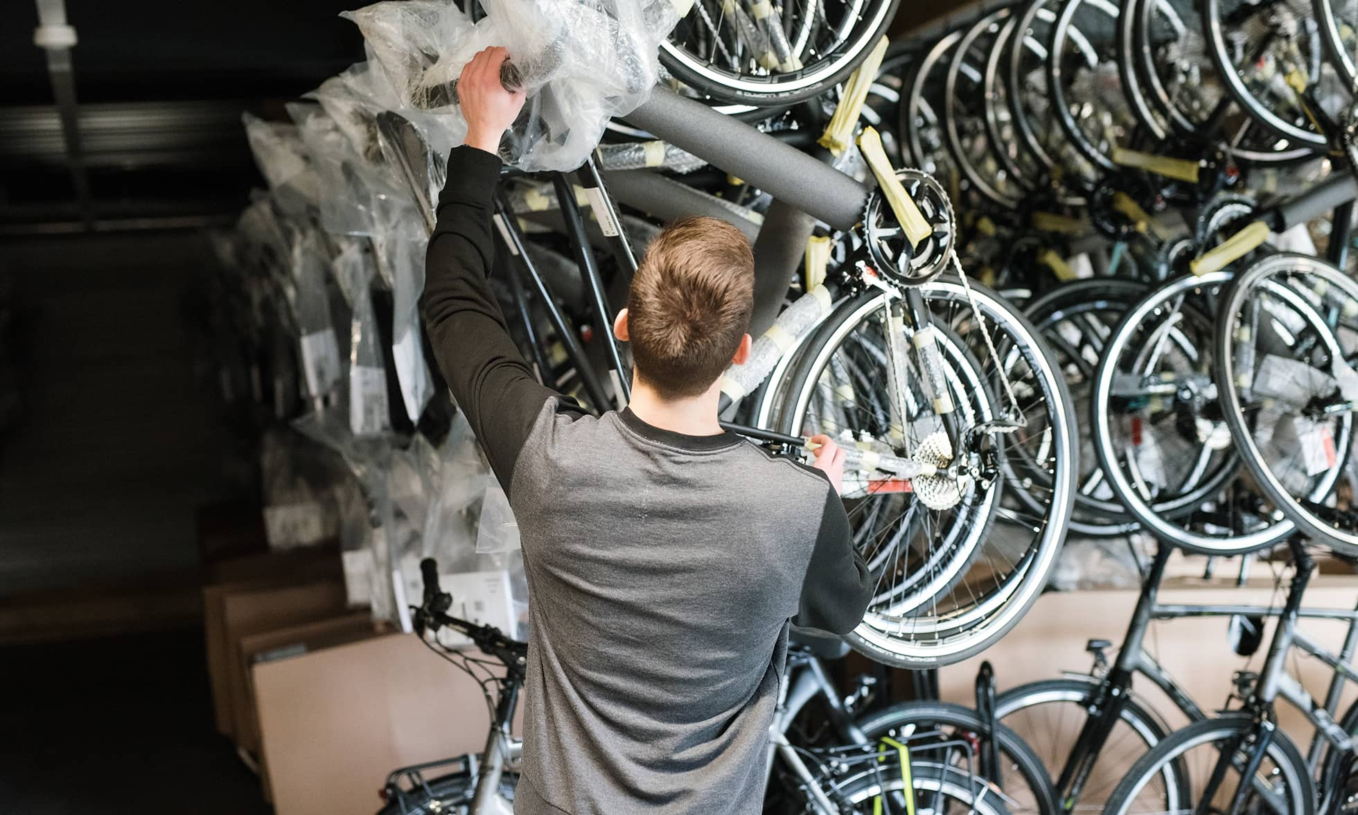 Employee takes new bicycle from vertical rack