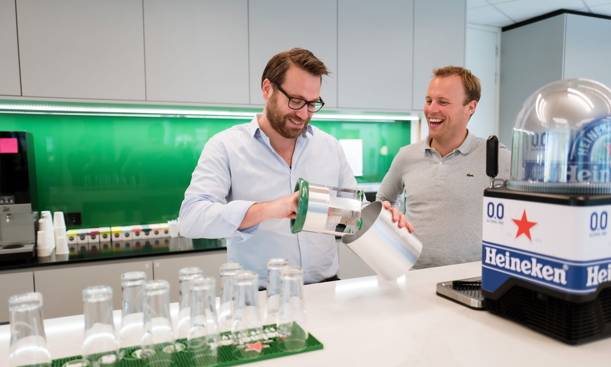 Two smiling men put together an accessory for the Heineken BLADE