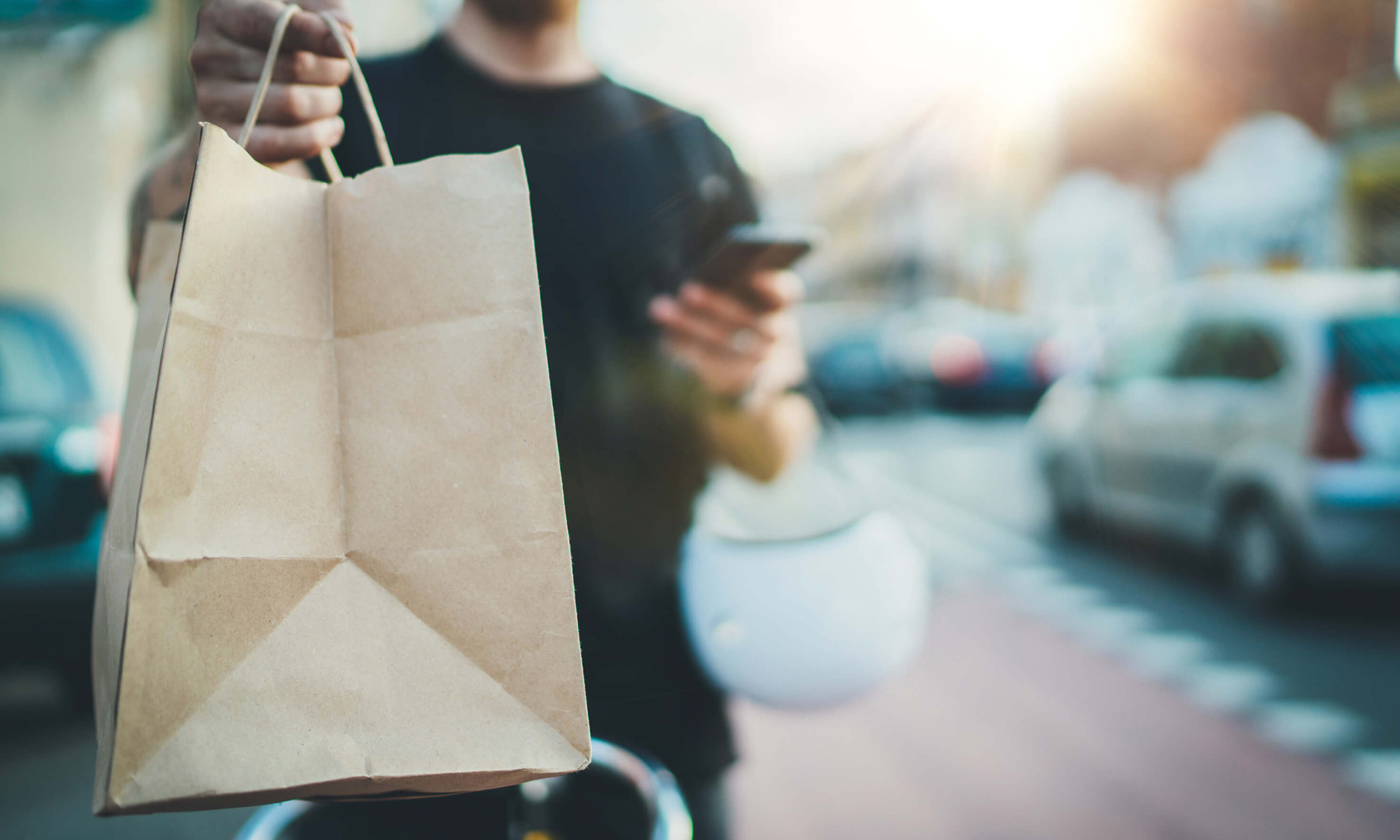 Close-up of a food delivery driver holding up a paper bag to the camera. In their other hand is a smartphone.