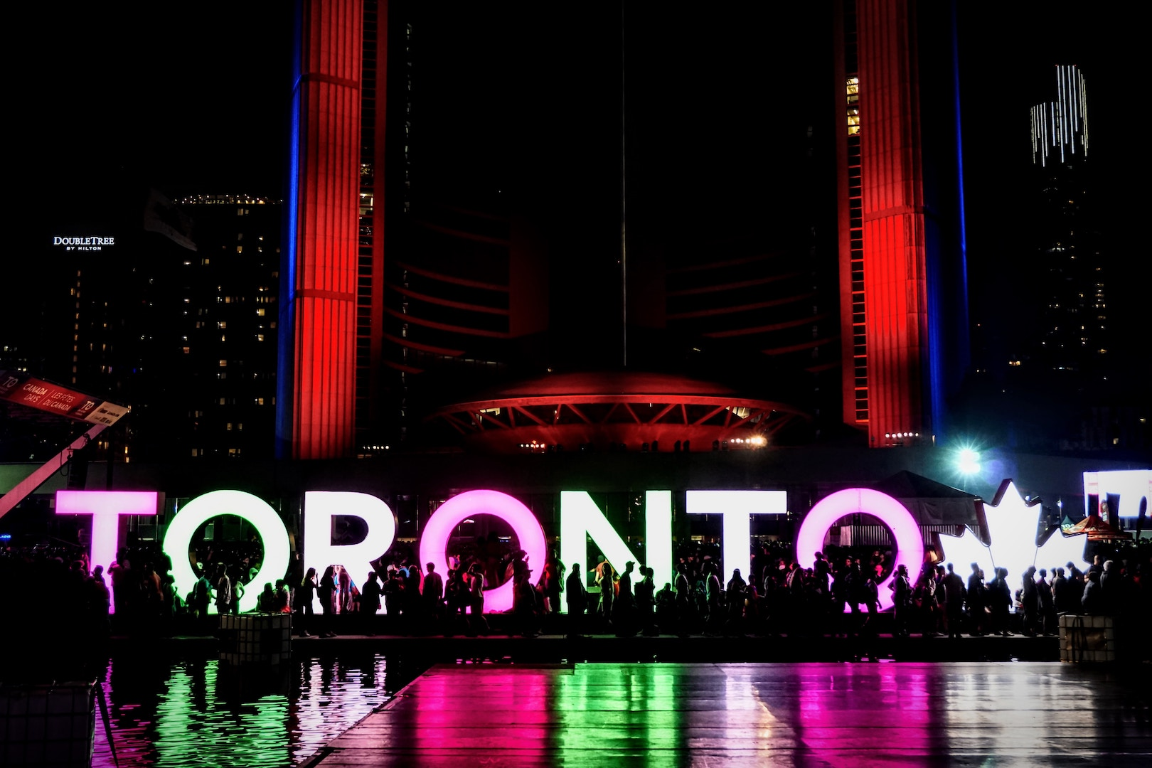 image of Toronto City Hall at night with LED Toronto sign and fireworks