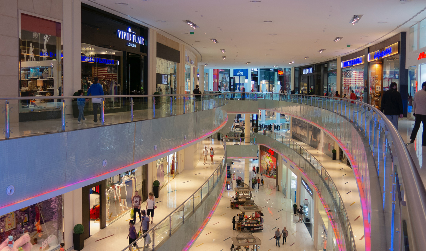 Interior of a shopping centre that has 3 levels and people are walking around shopping