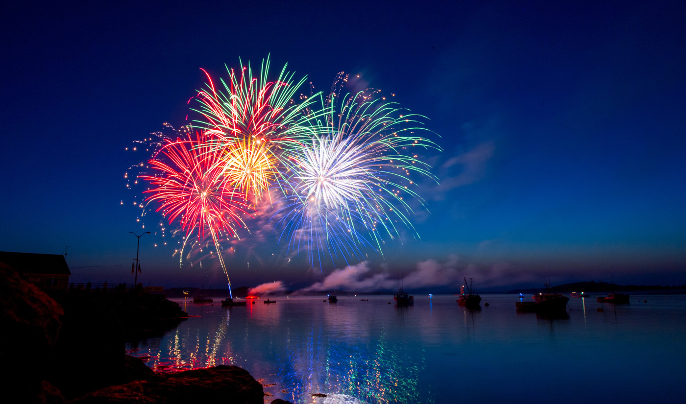 An assortment of colourful fireworks going off across a lake