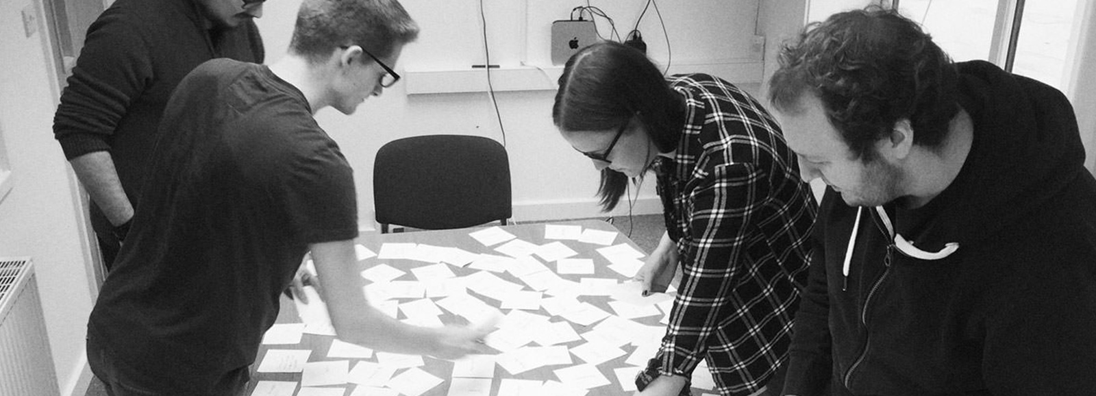 People stood around a table that is filled with notes during a UX design sprint