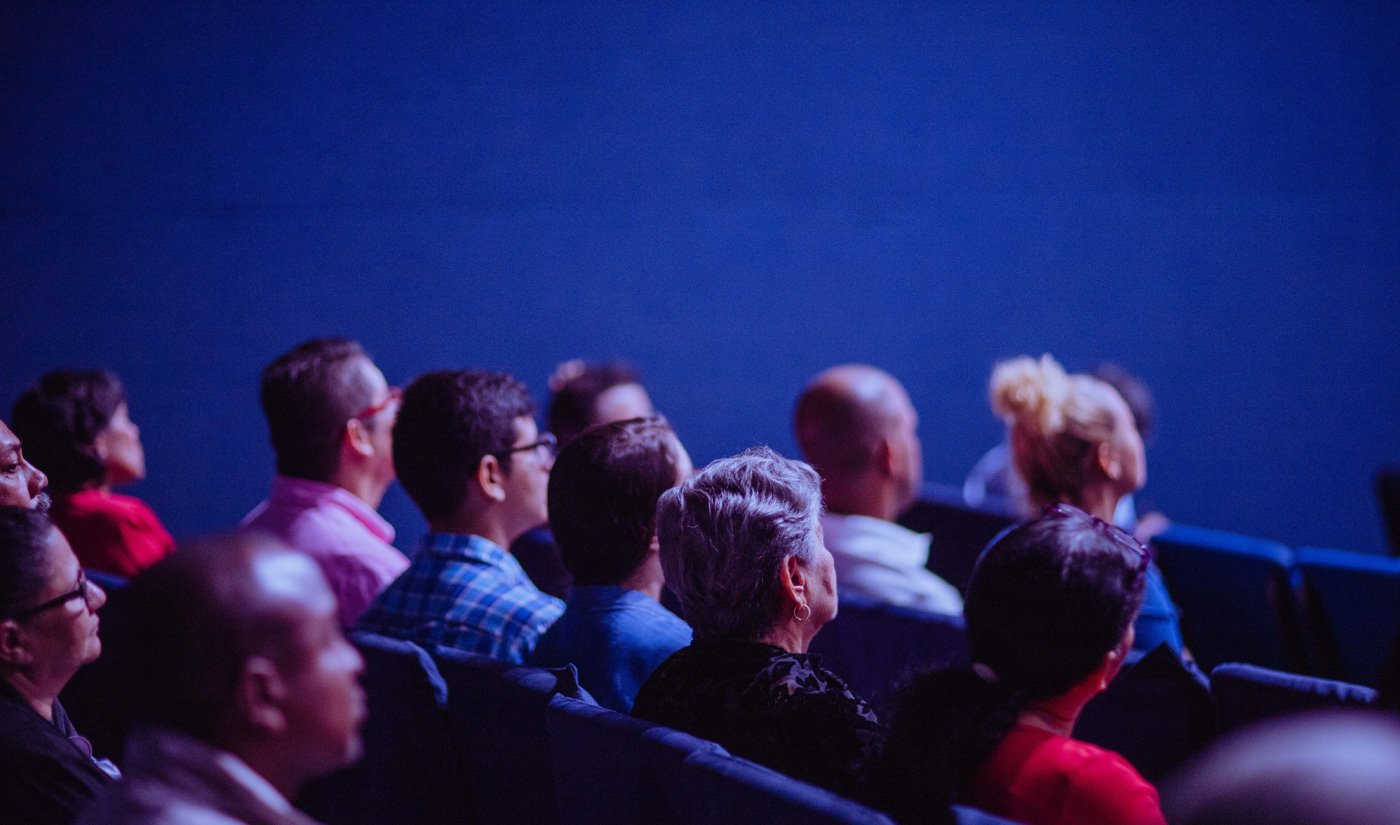 Numerous people sat down in a theatre hall with their backs to the camera