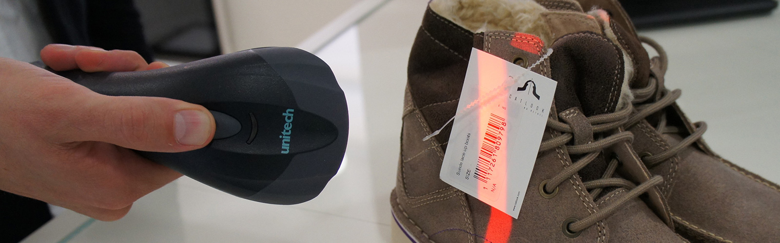Someone scanning a barcode on the label of some brown boots with a barcode scanner