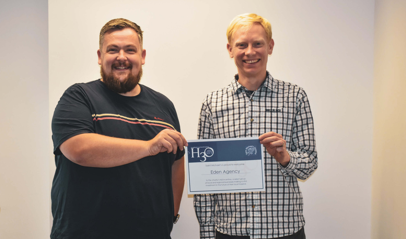 Eden directors Craig and Andy stood together holding a certificate awarded to Eden by our CSR charity partner