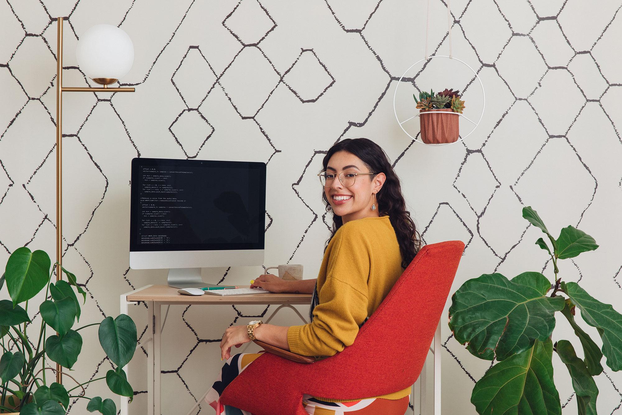 Programmer smiling at desk in home office.