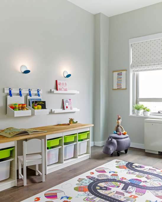 Lincoln Tower Apartment residential interior design renovation by Basicspace. Playful kids desk and wall storage with adjustable lighting. Art bins, baskets, shelving, and wall hooks for easy access to toys, arts and crafts, and books. Play mat and roman blackout shades complete the space.
