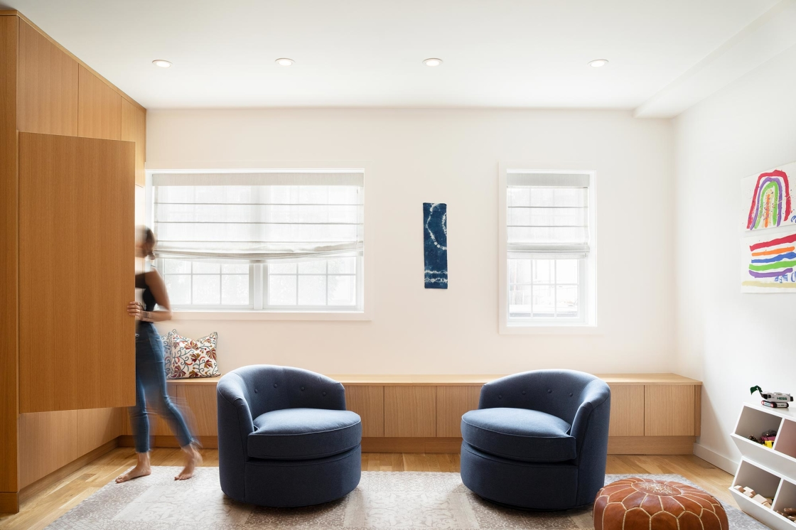 Jersey City Condo residential interior design by Basicspace. Contrasting white and warm wood with cozy navy blue swivel chair. Built-in closet storage and window bench seating for toys in kids playroom.
