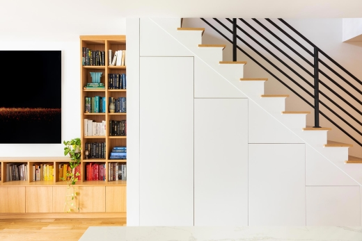 Jersey City Condo residential interior design by Basicspace. Contrast of white and wood alignment of storage elements. Under stair storage and open shelving with black metal stair banister.