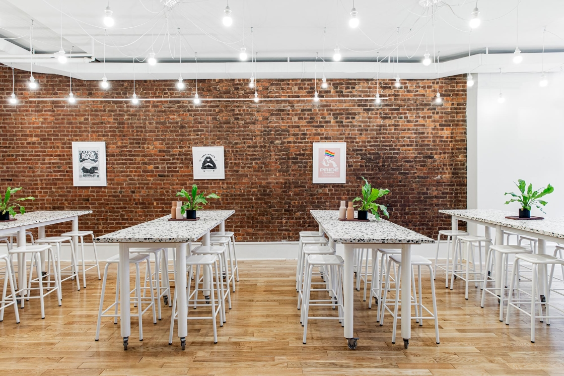 Maven Clinic office renovation interior design by Basicspace. All hands assembly white seating enveloped in the texture of brick and playful terrazzo custom tables on wheels. Hanging pendant lights, green ferns, and minimal art track finish the space