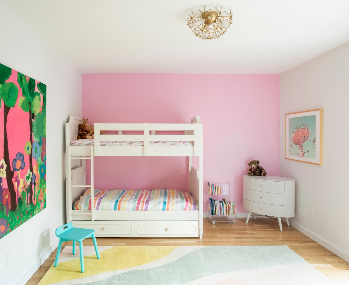 Jersey City Condo residential interior design by Basicspace. Pink girl's bedroom with large kid's art, flower ceiling light, rainbow rug and round dresser.