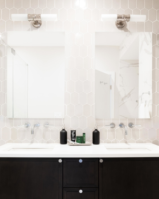 Jersey City Condo residential interior design by Basicspace. Master bathroom black and white double vanity, hexagon tile wall, wall-mounted faucets, medicine cabinet and sconces.